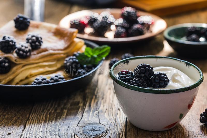 Crepes,yogurt in rural mug, fresh blackberries, healthy breakfast. Healthy breakfast or brunch, favorite morning meal. Homemade crepes, fresh summer blackberry stock photo