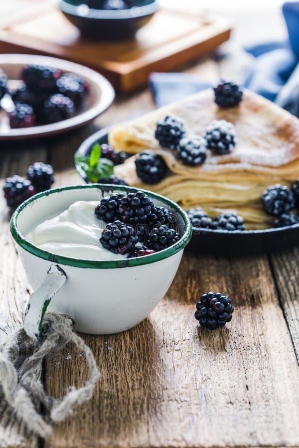 Crepes,yogurt in rural mug, fresh blackberries, healthy breakfast. Healthy breakfast or brunch, favorite morning meal. Homemade crepes, fresh summer blackberry stock image