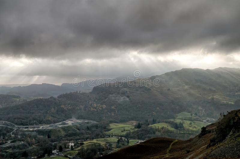 Crepuscular rays and the Great Langdale valley. Crepuscular rays and the Great Langdale valley, in the English Lake District stock image