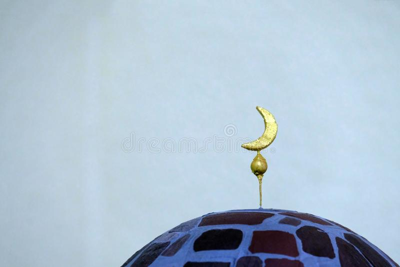 Crescent of handwork on the stone minaret. A close-up of the symbol of Islamic culture and religion. Light background. royalty free stock photo