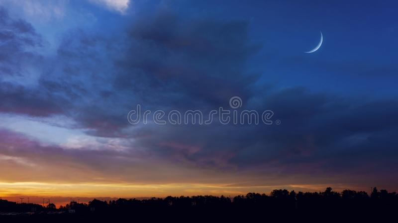 Crescent moon with beautiful sunset background . Generous Ramadan. Crescent moon with Stars . Sunrise . Light from sky . Religion background royalty free stock photo