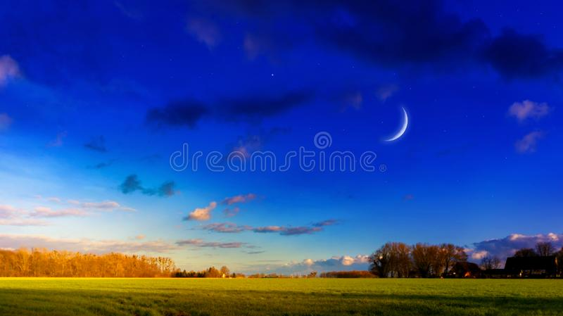 Crescent moon with beautiful sunset background . Generous Ramadan . Moon sun and stars . Light in dark sky . Beautiful landscape image of rural areas . new royalty free stock images