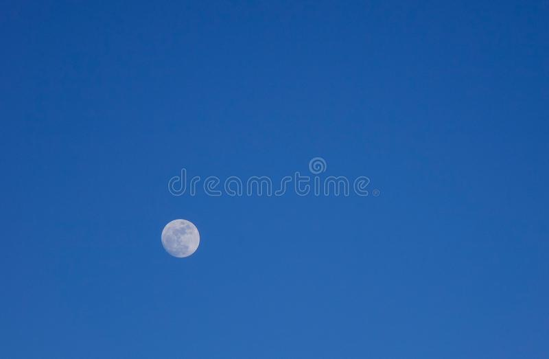 Moon in the blue sky stock photography