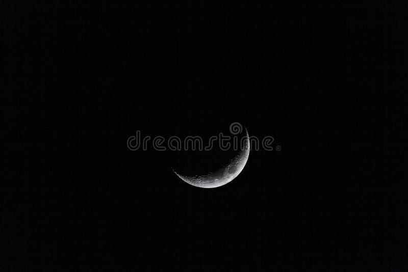 Crescent moon on a dark sky stock image