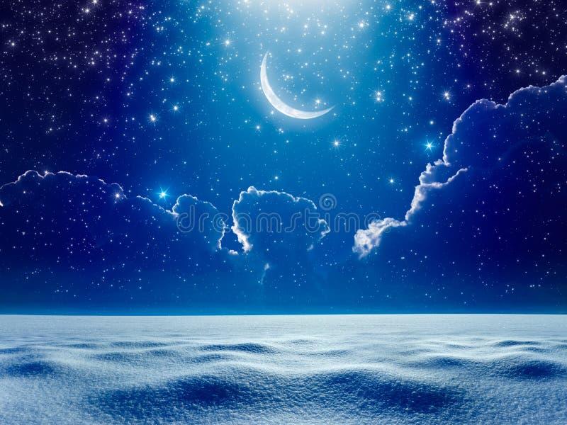 Crescent moon in dark blue night starry sky above snowy field, b stock image