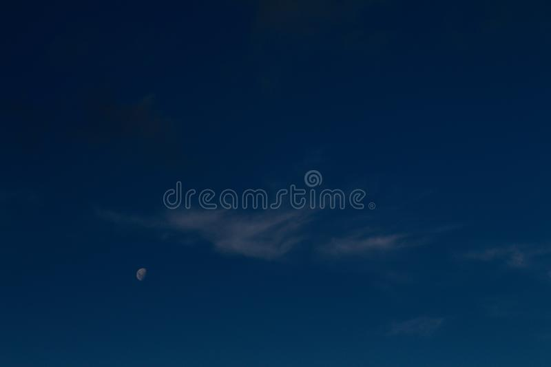 Crescent moon, next to a small white cloud royalty free stock photo