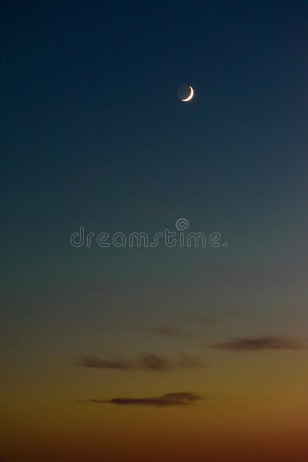 Crescent moon after orange sunset. Crescent moon after beautiful orange sunset royalty free stock photo
