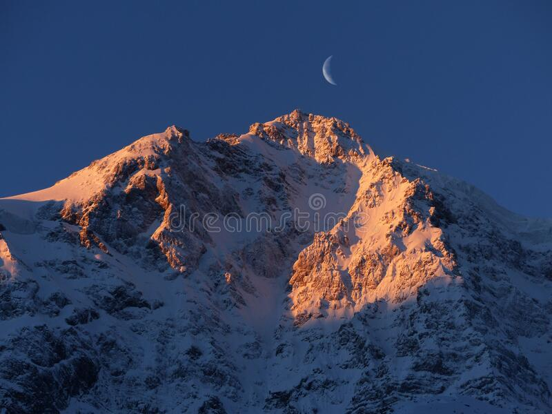 Crescent Moon over Snow Mountain stock photography