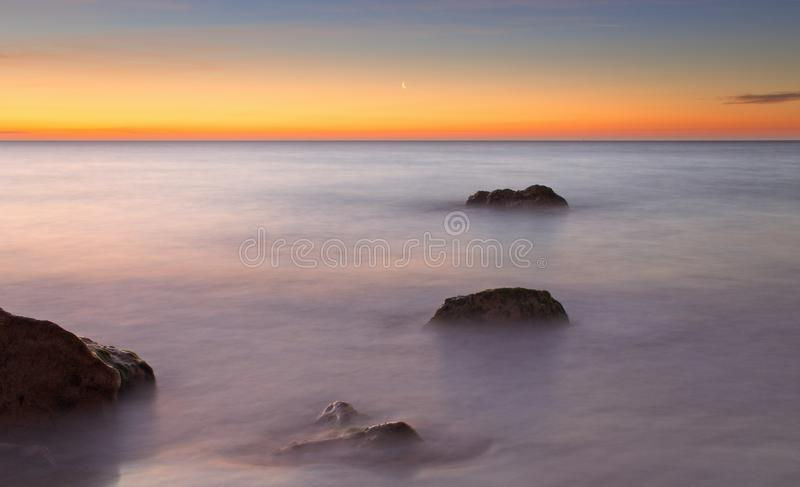Crescent moon at sunrise with beautiful red sky, calm sea with rocks in foreground, port nou, cala bona, mallorca, spain royalty free stock images