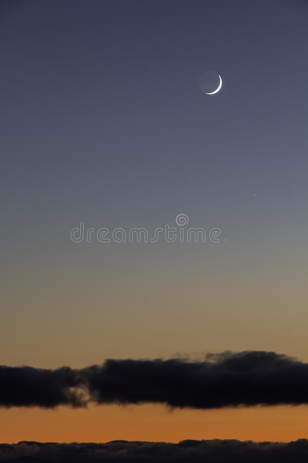 Crescent moon at sunset. Beautiful crescent moon at sunset over clouds and mountains stock image