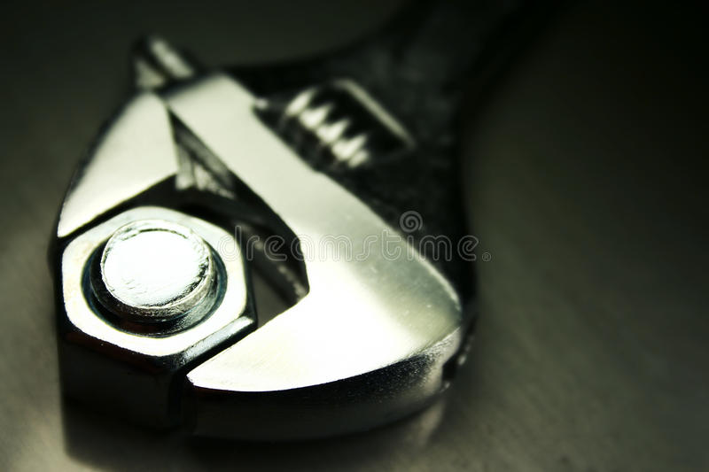 Crescent wrench. Macro of a crescent wrench against a dark metallic background stock photos