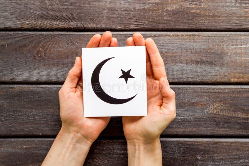 Crescente símbolo islâmico e estrela em mãos na vista de cima da mesa de madeira imagens de stock royalty free