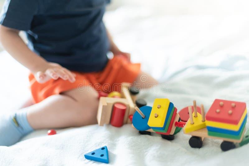 Crescere e concetto di svago dei bambini Un bambino che gioca con un treno di legno colorato Il bambino costruisce il costruttore immagini stock
