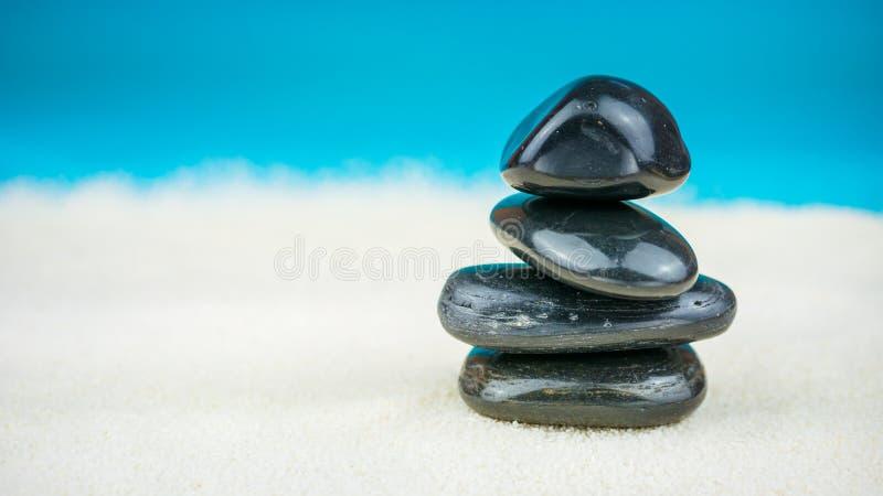 Crescita accatastato su dei ciottoli neri sulla sabbia luminosa con fondo blu fotografie stock
