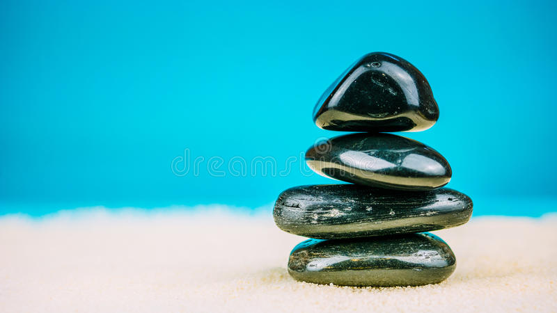 Crescita accatastato su di quattro ciottoli neri sulla sabbia luminosa con fondo blu fotografie stock