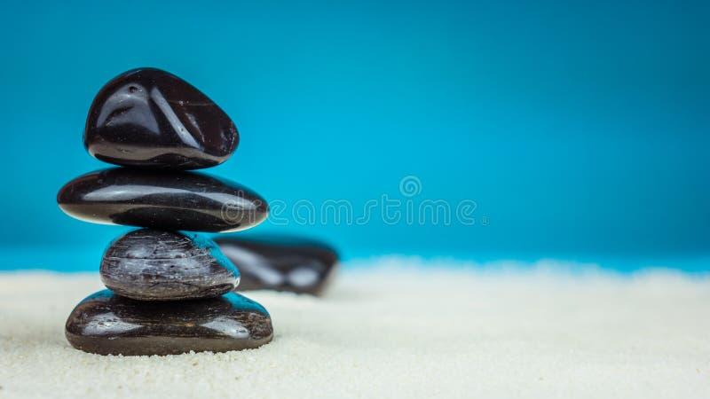 Crescita accatastato su di quattro ciottoli neri sulla sabbia luminosa con fondo blu immagine stock