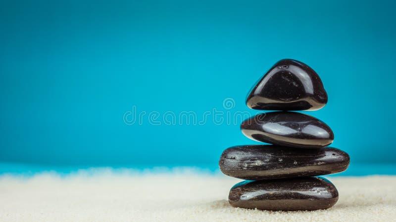 Crescita accatastato su di quattro ciottoli neri sulla sabbia luminosa con fondo blu immagini stock