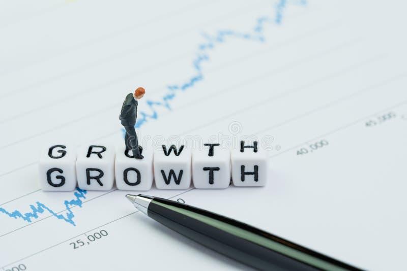 Crescita di affari o restituire aumento nel concetto di investimento, condizione miniatura dell'uomo d'affari sul blocchetto del  fotografia stock