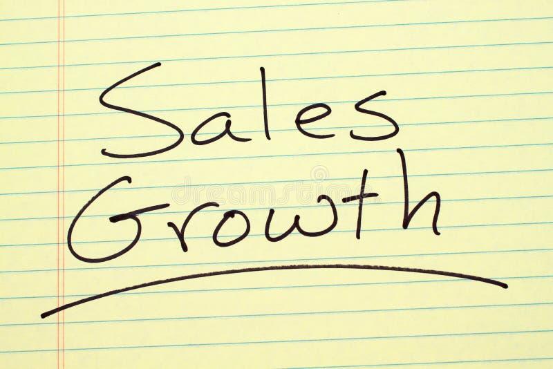Crescita di vendite su un blocco note giallo immagine stock