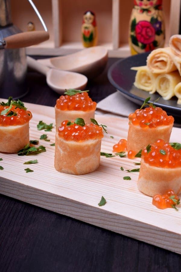 Crespones con el caviar rojo en un tablero de madera asperjado con perejil foto de archivo libre de regalías