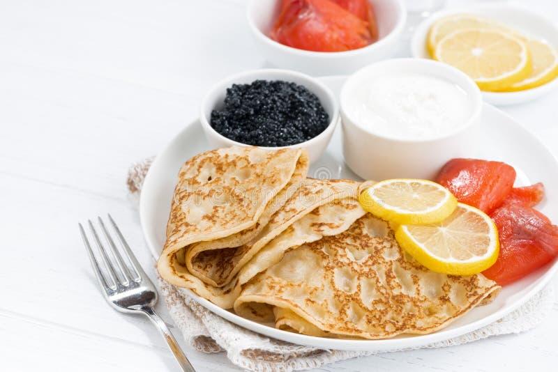 Crespones con los pescados, la crema agria y el caviar salados, primer imagenes de archivo