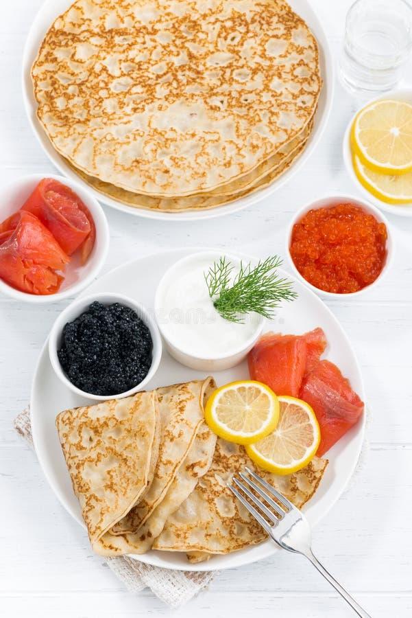 Crespones con los pescados, la crema agria y el caviar, visión superior imagen de archivo libre de regalías