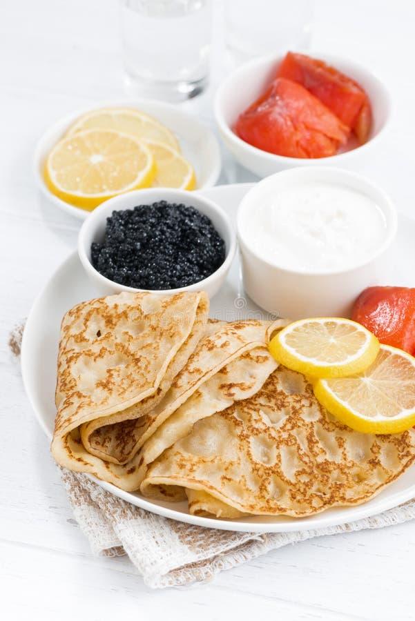 Crespones con los pescados salados, crema agria y caviar, verticales imagenes de archivo