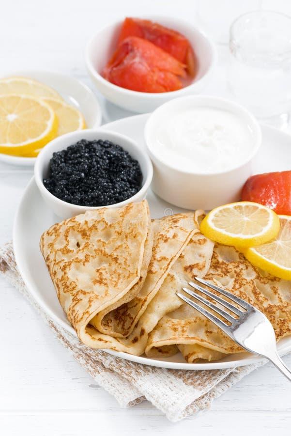 Crespones con los pescados salados, crema agria y caviar, verticales fotografía de archivo
