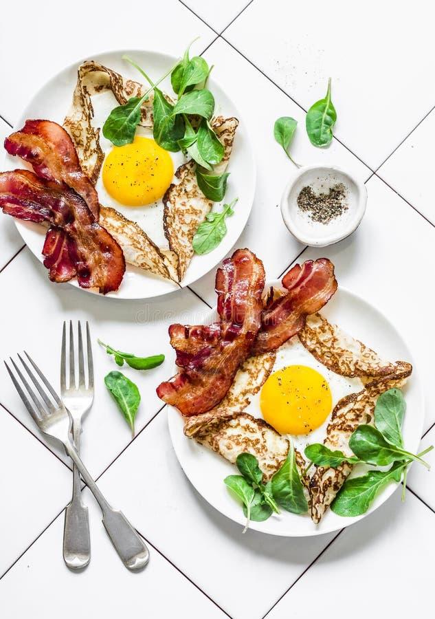 Crespones del huevo relleno con el tocino y el arugula - brunch nutritivo delicioso en un fondo ligero, visión superior Endecha p imagen de archivo libre de regalías