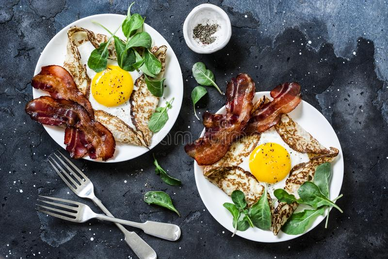 Crespones del huevo relleno con el tocino y el arugula - brunch nutritivo delicioso en un fondo oscuro, visión superior Endecha p foto de archivo