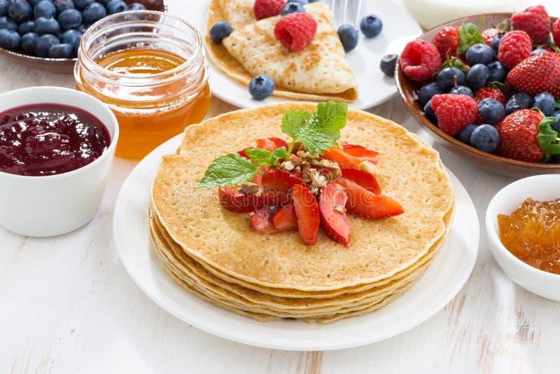 Crespones deliciosos con las fresas y la miel en la tabla blanca fotos de archivo libres de regalías