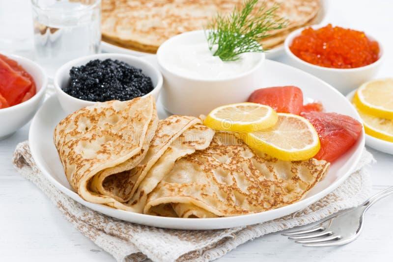 Crespones rusos tradicionales con el caviar y los pescados salados imagen de archivo libre de regalías