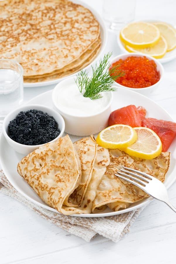 Crespones tradicionales con los pescados, crema agria y caviar, verticales imagenes de archivo