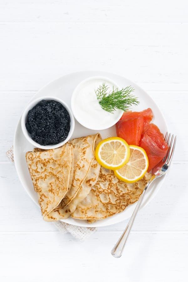 Crespones tradicionales con los pescados, la crema agria y el caviar, visión superior imagenes de archivo
