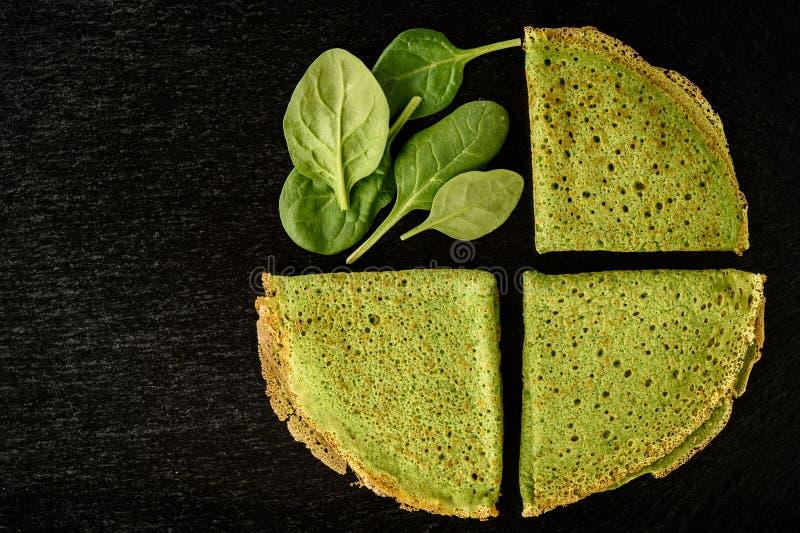 Crespones verdes de las crepes de la espinaca en fondo negro imagen de archivo