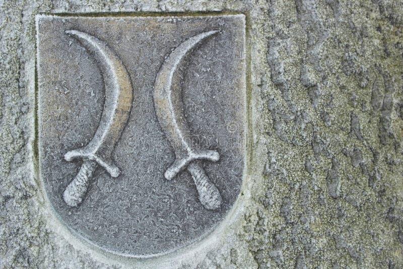 Cresta con i pugnali sulla parete di pietra immagine stock libera da diritti