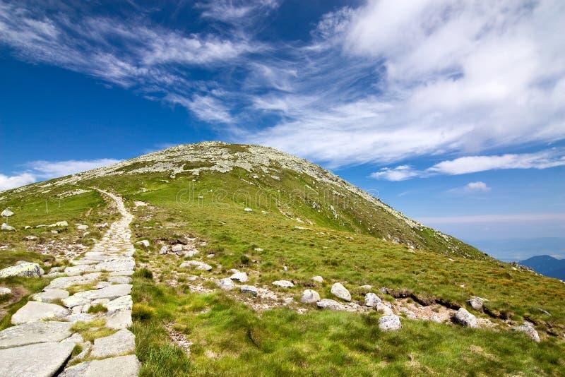 Cresta e cielo blu della montagna con le nubi fotografia stock libera da diritti