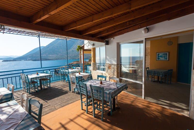 Creta de Bali, ilha, Grécia, - 23 de junho de 2016: As tabelas no restaurante com vista no mar Mediterrâneo e nas montanhas imagem de stock royalty free
