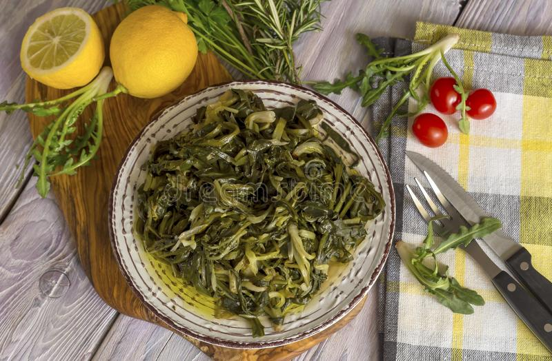 A dish of rare boiled grass `stamnagathi`Cichorium spinosum. Cretan cuisine. A dish of rare, wild, useful boiled grass `stamnagathi` Cichorium spinosum, that stock photos