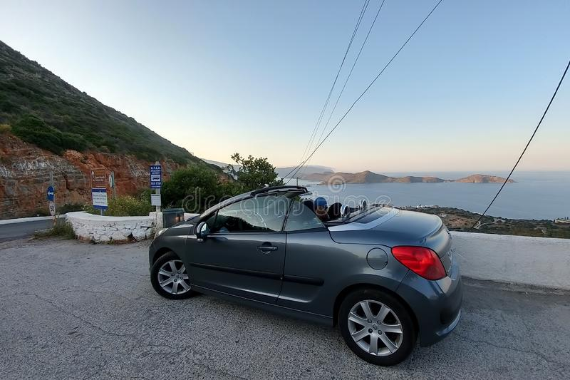 Crete. Greece - April 1, 2019: The girl and the cabriolet stand in front of a stunning panoramic view. Sea and winding mountain. Road, serpentine car travel stock photos