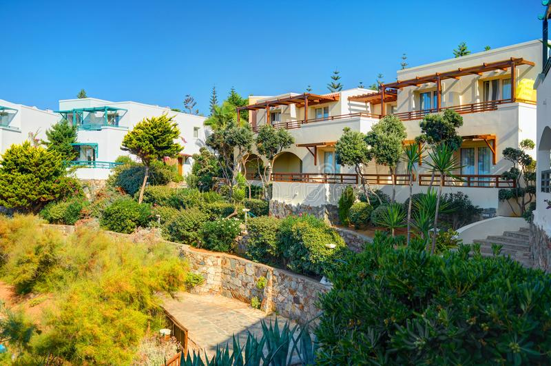 CRETE ISLAND, GREECE, SEP 08, 2012: Classical Greece hotel villa on stone beach among green trees for tourists guests. Luxury Gree stock photo