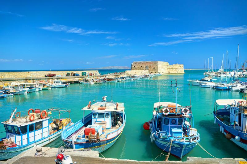 CRETE ISLAND, GREECE, SEP 12, 2012: View on beautiful classic old piscatory small sea boats ships, white yachts, Heraklion Greek s stock image