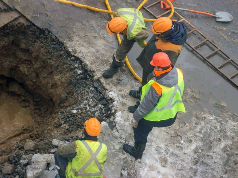Creusement d'un trou pour éliminer la fuite des tuyaux au milieu de l'hiver images libres de droits