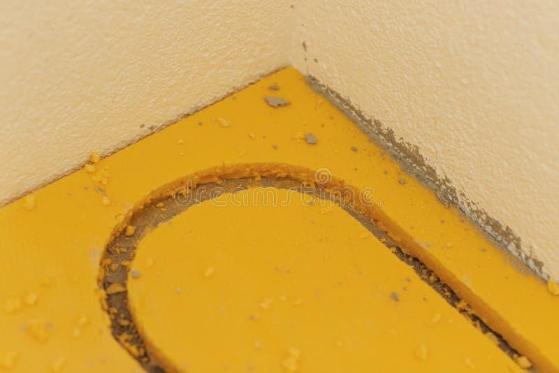 Creusez le plancher rigide jaune de mousse en préparation d'étendre le chauffage par le sol photographie stock