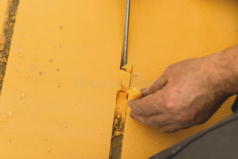 Creusez le plancher rigide jaune de mousse en préparation d'étendre le chauffage par le sol images stock