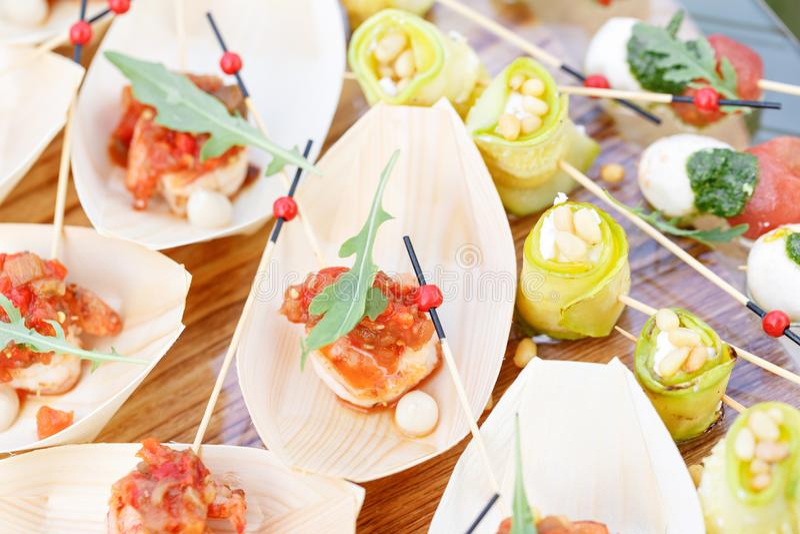 Crevette délicieuse et tomates coupées en tranches sur un bateau en bois La courgette roule avec des pignons Table de buffet savo photo libre de droits