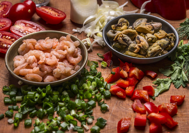 Crevette et moules épluchées avec des tomates de poivre coupé et d'oignons verts une fin en bois de fond  photos libres de droits