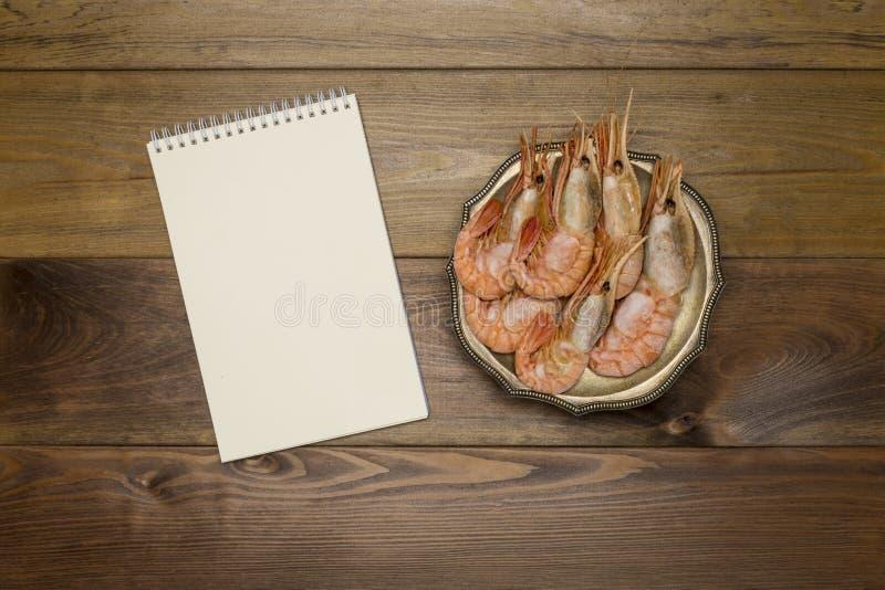 Crevettes de roi de plat avec le bloc-notes au fond en bois images libres de droits