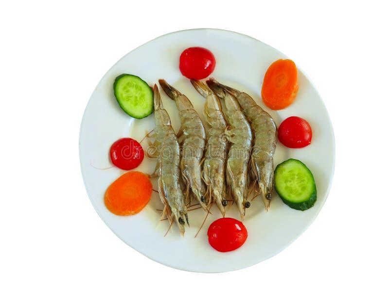 Crevettes de tigres avec légumes dans une assiette isolée sur blanc photos stock