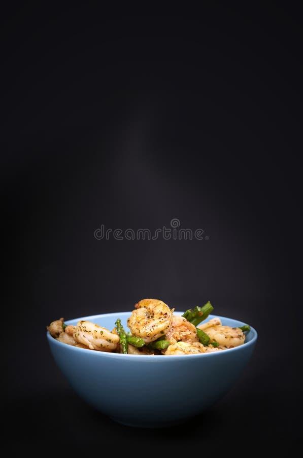 Crevettes et asperge frites dans une cuvette images libres de droits